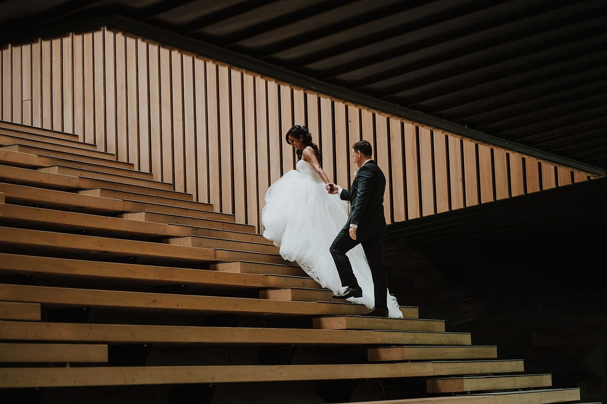 wedding couple walking up stairs outside Audain Art Museum