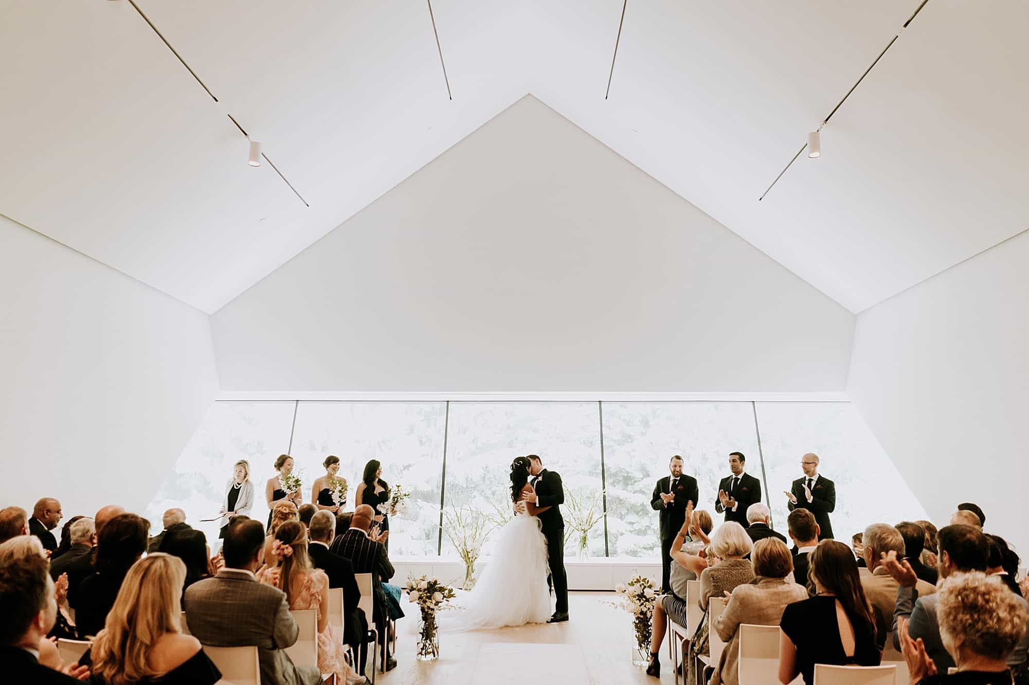 first kiss at wedding ceremony in upper gallery of audain